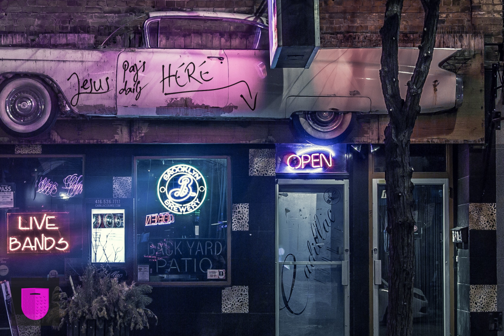 Bildnachweis: Entrance to a music venue in neon light by Matthew Henry Unsplash.com License, bearbeitet von Simon Mallow.
