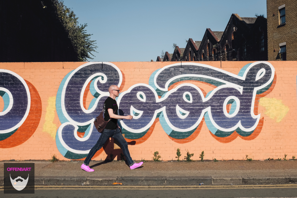 "Bildnachweis: Bald man wearing pink shirt and sunglasses walks on sidewalk in front of graffiti that reads ""good"" by Volkan Olmez Unsplash.com License, bearbeitet von Lukas Klette."